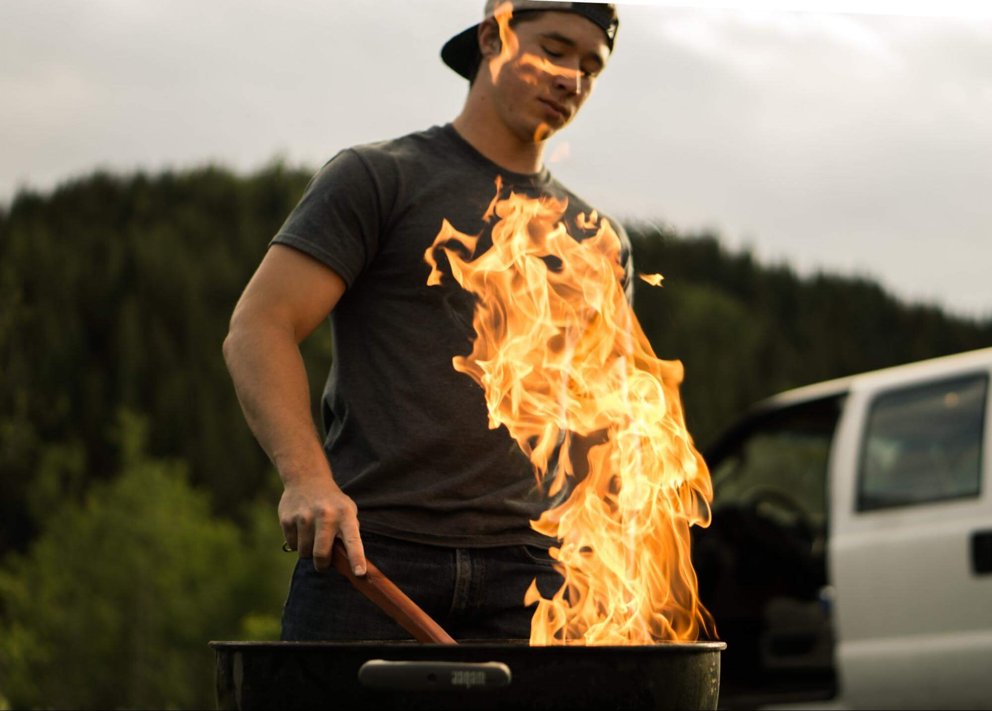 Man grilling over open flame grill